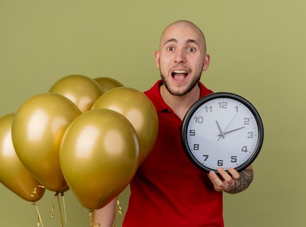 Pod wrażeniem młody przystojny słowiański partyjny facet stojący w pobliżu balonów trzymając zegar patrząc na kamery na białym tle na oliwkowym tle