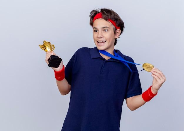 Pod wrażeniem młody przystojny sportowy chłopiec noszący opaskę i opaski na nadgarstek z szelkami dentystycznymi i medalem na szyi, trzymając puchar zwycięzcy i medal patrząc z boku na białym tle na białej ścianie