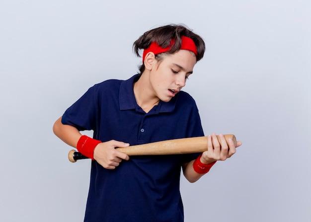 Pod wrażeniem młody przystojny sportowy chłopiec noszący opaskę i opaski na nadgarstki z aparatami ortodontycznymi trzymający i patrząc na kij baseballowy na białej ścianie