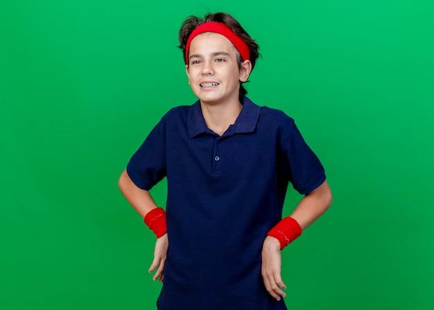 Pod wrażeniem młody przystojny sportowy chłopiec noszący opaskę i opaski na nadgarstki z aparatami ortodontycznymi trzymający ręce w talii, patrząc prosto na białym tle na zielonym tle z przestrzenią do kopiowania