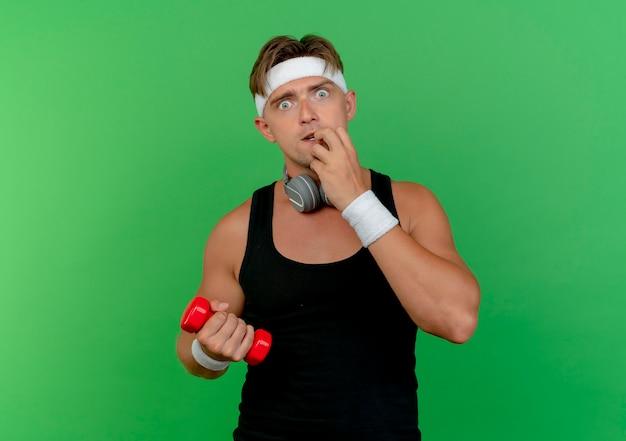 Pod wrażeniem młody przystojny sportowy mężczyzna noszący opaskę i opaski na rękę ze słuchawkami na szyi trzymający hantle kładąc palce na wardze odizolowanej na zielono
