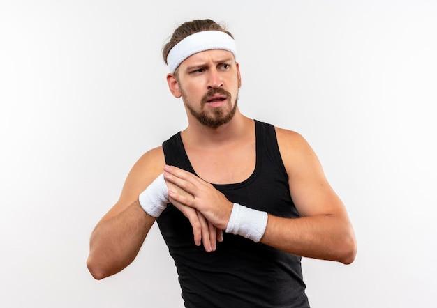 Pod wrażeniem młody przystojny sportowy mężczyzna noszący opaskę i opaski, patrząc na bok, kładąc rękę na innym odizolowanym na białej ścianie