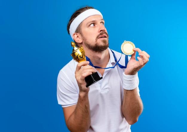 Pod wrażeniem młody przystojny sportowy mężczyzna noszący opaskę na głowę, opaski i medal na szyi, trzymający medal i puchar zwycięzcy, patrząc na stronę odizolowaną na niebieskiej ścianie z miejscem na kopię