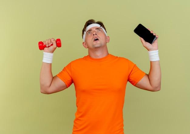 Pod wrażeniem młody przystojny sportowy mężczyzna ubrany w opaskę i opaski na rękę trzymając telefon komórkowy i hantle patrząc w górę na białym tle na oliwkową zieleń