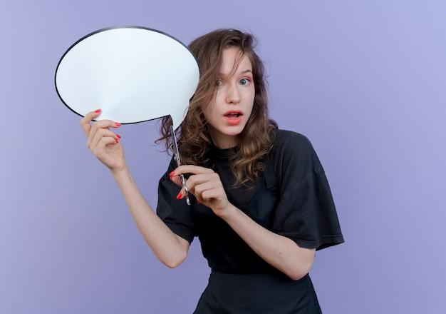 Pod wrażeniem młody słowiański fryzjer kobieta ubrana w mundur trzymając bańkę czatu i nożyczki na białym tle na fioletowym tle z miejsca na kopię