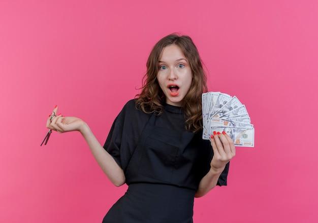 Pod wrażeniem młody słowiański fryzjer kobieta ubrana w mundur trzymając pieniądze i nożyczki na białym tle na różowym tle