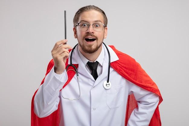 Pod wrażeniem młody superbohater facet ubrany w szlafrok medyczny ze stetoskopem i okularami trzymając ołówek