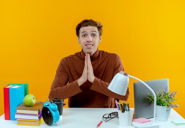 Pod wrażeniem młody uczeń chłopiec siedzi przy biurku z narzędziami szkolnymi, pokazując gest módl się