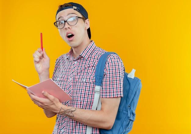 Pod wrażeniem młody uczeń chłopiec ubrany z powrotem torbę i okulary i czapkę trzymając notatnik i długopis na białym tle