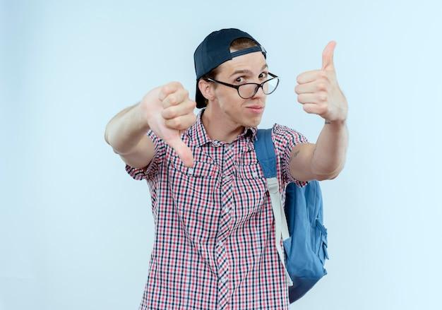 Pod wrażeniem młody uczeń w plecaku i okularach i czapce kciukami w górę iw dół