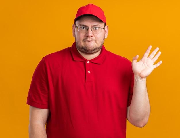 Pod wrażeniem nadwagi młody doręczyciel w okularach optycznych stojący z podniesioną ręką odizolowaną na pomarańczowej ścianie z miejscem na kopię