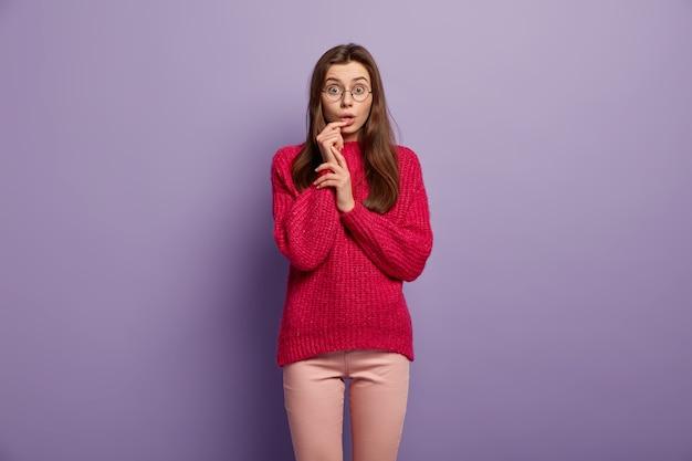 Pod wrażeniem nastolatka trzyma rękę przy otwartych ustach, patrzy ze zdziwieniem, nosi okrągłe okulary, czerwony sweter, odizolowany na fioletowej ścianie ludzie, reakcja, mimika
