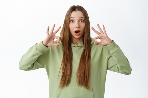 Pod wrażeniem nastolatka wzdycha i pokazuje dobry znak, chwali coś imponującego, komplementuje niesamowite wydarzenie, wykonuje ok gest, zatwierdza i lubi, stań nad białą ścianą