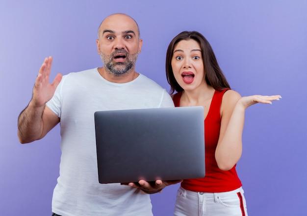 Pod wrażeniem para dorosłych patrząc trzymając laptopa pokazując pustą rękę