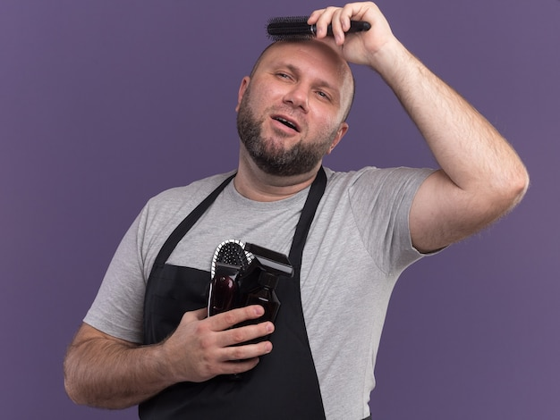Pod wrażeniem patrząc na bocznego słowiańskiego mężczyznę w średnim wieku w mundurze, trzymającego narzędzia fryzjerskie i czesającego włosy na fioletowej ścianie