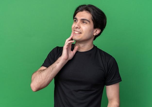 Pod wrażeniem patrząc na bok młody przystojny facet ubrany w czarną koszulkę kładąc dłoń na policzku na białym tle na zielonej ścianie
