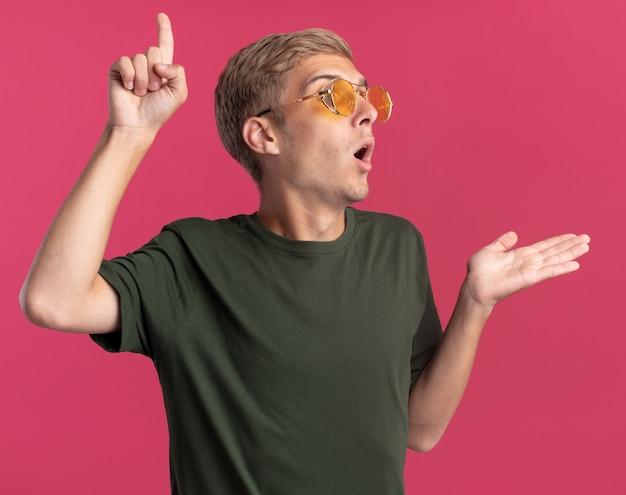 Pod wrażeniem patrząc na bok młody przystojny facet w zielonej koszuli i okularach wskazuje ręką na boku na białym tle na różowej ścianie