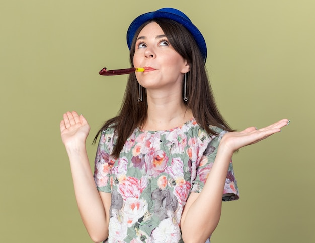 Pod wrażeniem, patrząc na młodą, piękną kobietę w kapeluszu imprezowym, dmuchający gwizdek, rozkładający ręce na oliwkowozielonej ścianie