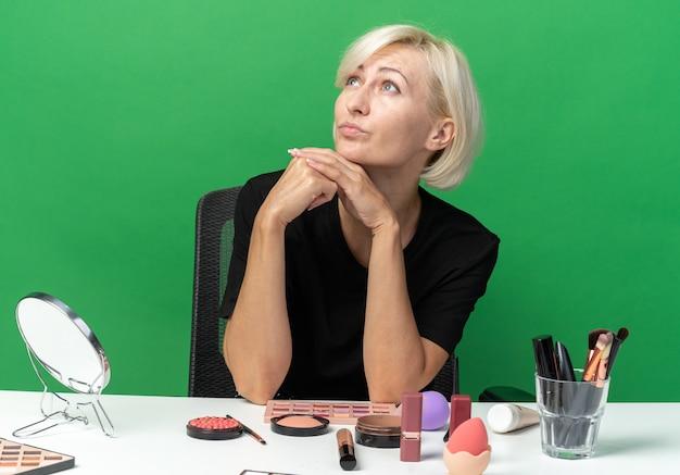 Pod wrażeniem, patrząc w górę, młoda piękna dziewczyna siedzi przy stole z narzędziami do makijażu, kładąc ręce pod brodą na zielonej ścianie