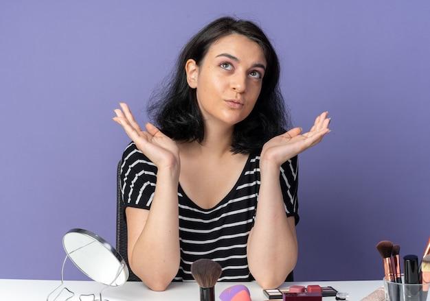 Pod wrażeniem, patrząc w górę, młoda piękna dziewczyna siedzi przy stole z narzędziami do makijażu rozkładającymi ręce izolowane na niebieskiej ścianie