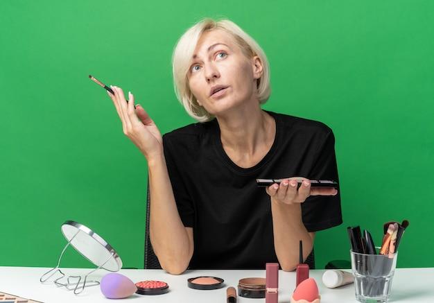 Pod wrażeniem, patrząc w górę, młoda piękna dziewczyna siedzi przy stole z narzędziami do makijażu, trzymając paletę cieni do powiek z pędzlem do makijażu na zielonej ścianie