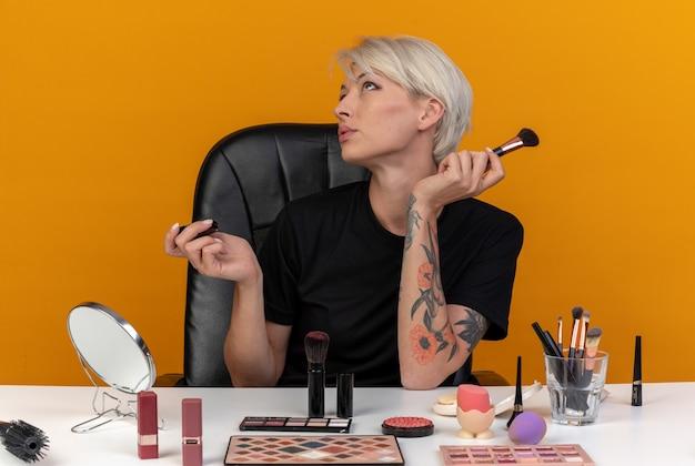 Pod wrażeniem, patrząc w górę, młoda piękna dziewczyna siedzi przy stole z narzędziami do makijażu, trzymając pędzel do pudru na białym tle na pomarańczowej ścianie