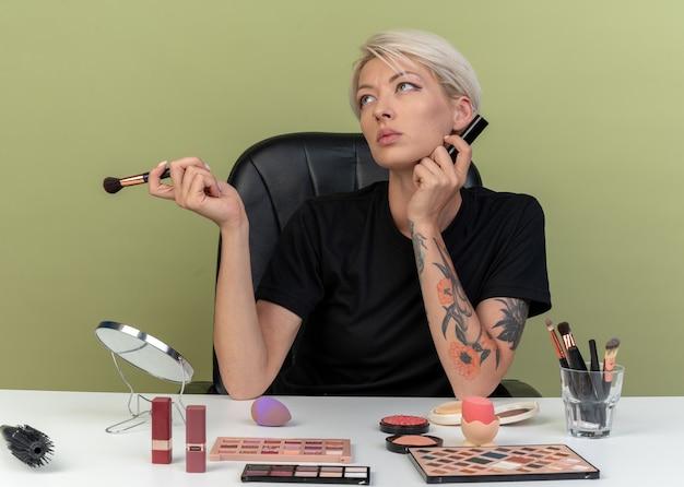 Pod wrażeniem, patrząc w górę, młoda piękna dziewczyna siedzi przy stole z narzędziami do makijażu, trzymając pędzel do pudru z pędzlem do makijażu odizolowaną na oliwkowozielonej ścianie