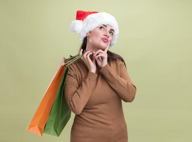 Pod wrażeniem, patrząc w górę młoda piękna dziewczyna ubrana w świąteczny kapelusz trzymając torbę na prezent na ramieniu na białym tle na oliwkowym tle