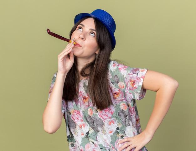 Pod wrażeniem, patrząc w górę, młoda piękna dziewczyna w kapeluszu imprezowym dmuchająca gwizdek kładąca rękę na biodrze