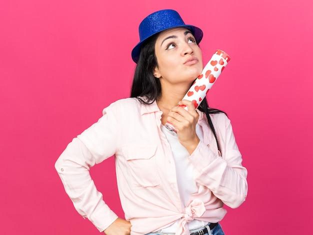 Pod wrażeniem, patrząc w górę, młoda piękna dziewczyna w kapeluszu imprezowym, trzymająca armatę konfetti, kładąc rękę na biodrze