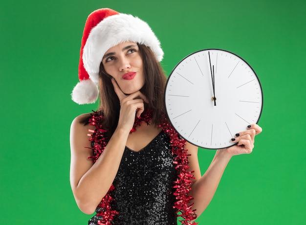 Pod wrażeniem, patrząc w górę młoda piękna dziewczyna w świątecznym kapeluszu z girlandą na szyi, trzymając zegar ścienny kładąc palec na policzku na białym tle na zielonym tle