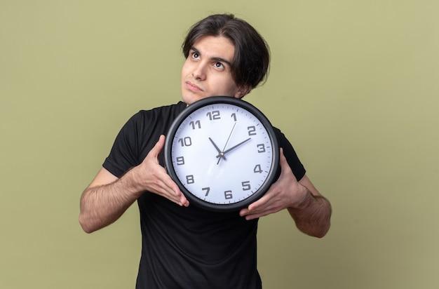 Pod wrażeniem, patrząc w górę młody przystojny facet ubrany w czarną koszulkę, trzymając zegar ścienny na białym tle na oliwkowej ścianie