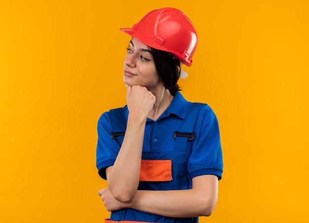 Pod wrażeniem, patrząc z boku, młoda kobieta budowlana w mundurze, kładąc rękę pod brodą, odizolowaną na żółtej ścianie