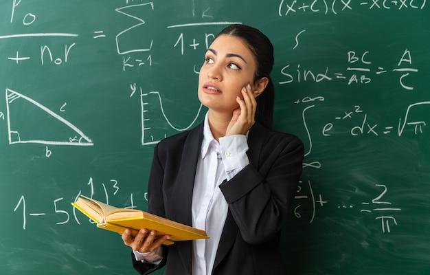 Pod wrażeniem, patrząc z boku, młoda nauczycielka stojąca przed tablicą trzymająca książkę, kładąc dłoń na policzku w klasie