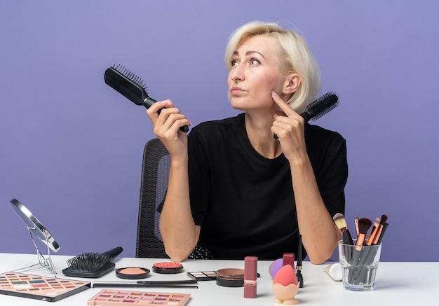 Pod wrażeniem, patrząc z boku, młoda piękna dziewczyna siedzi przy stole z narzędziami do makijażu, trzymając grzebienie izolowane na niebieskiej ścianie