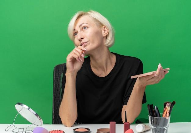 Pod wrażeniem, patrząc z boku, młoda piękna dziewczyna siedzi przy stole z narzędziami do makijażu, trzymając paletę cieni do powiek z pędzlem do makijażu na zielonej ścianie