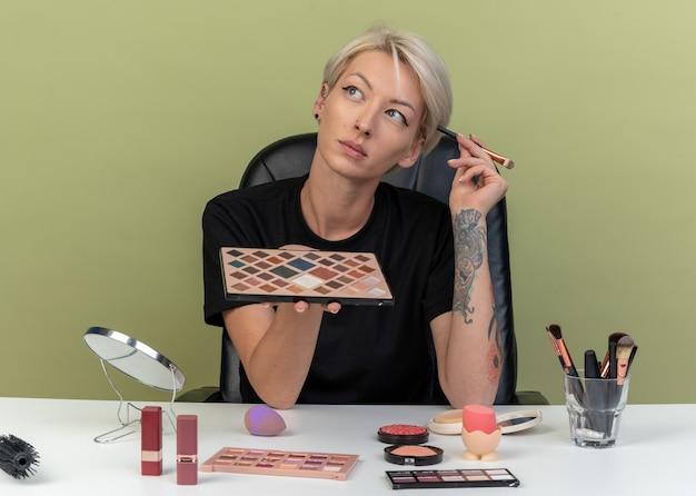 Pod wrażeniem, patrząc z boku, młoda piękna dziewczyna siedzi przy stole z narzędziami do makijażu, trzymając paletę cieni do powiek z pędzlem do makijażu odizolowaną na oliwkowozielonej ścianie