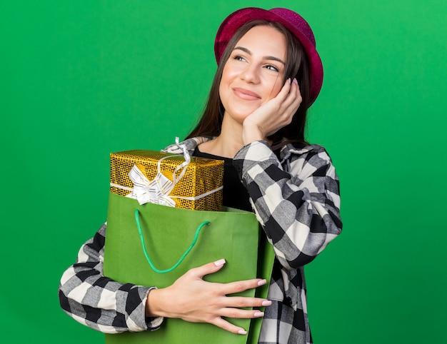 Pod wrażeniem, patrząc z boku, młoda piękna dziewczyna w kapeluszu imprezowym, trzymająca torbę z prezentami, kładąc rękę na policzku