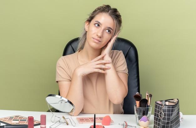 Pod wrażeniem patrząca na bok młoda piękna dziewczyna siedzi przy biurku z narzędziami do makijażu, kładąc rękę na policzku odizolowaną na oliwkowozielonej ścianie
