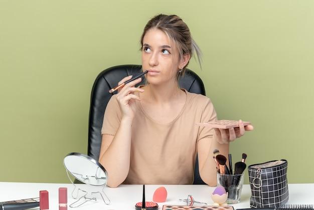 Pod wrażeniem patrząca na bok młoda piękna dziewczyna siedzi przy stole z narzędziami do makijażu, trzymając pędzel z paletą cieni do powiek odizolowaną na oliwkowozielonej ścianie