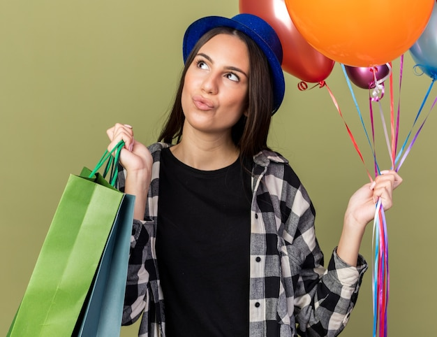 Pod wrażeniem patrząca na bok młoda piękna dziewczyna w niebieskim kapeluszu, trzymająca balony z torbą na prezent