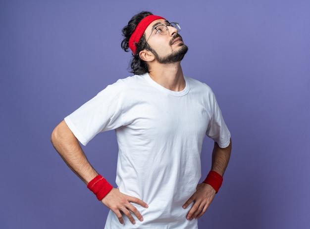 Pod wrażeniem patrzącego w górę młodego wysportowanego mężczyzny noszącego opaskę z opaską na nadgarstku, kładącej ręce na biodrze