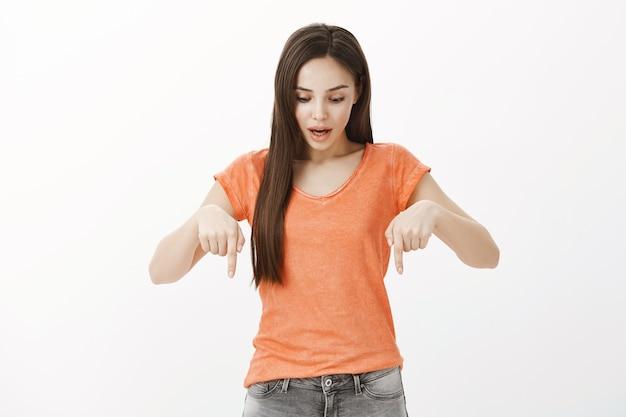 Pod wrażeniem piękna brunetka wskazująca palcami w dół, wygląda na zdumioną