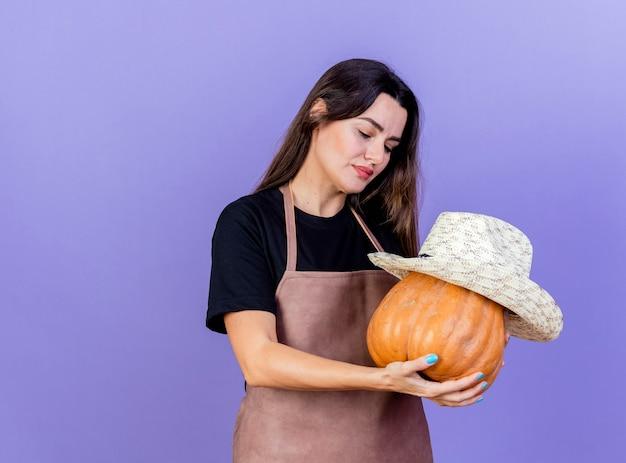 Pod wrażeniem piękna dziewczyna ogrodnik w mundurze, trzymając i patrząc na dyni w kapeluszu na białym tle na niebieskim tle