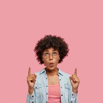 Pod wrażeniem piękna kobieta pozuje na różowej ścianie