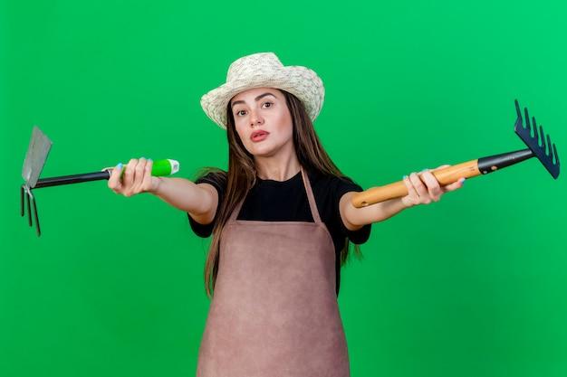 Pod wrażeniem piękna ogrodniczka dziewczyna w mundurze w kapeluszu ogrodniczym, trzymając grabie z grabiami motyki w aparacie na białym tle na zielonym tle