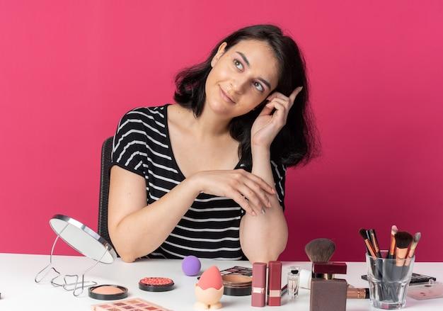 Pod wrażeniem pochylania głowy młoda piękna dziewczyna siedzi przy stole z narzędziami do makijażu odizolowanymi na różowej ścianie