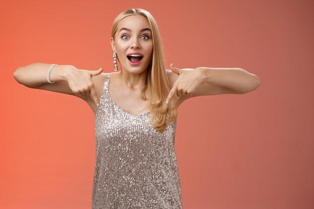 Pod wrażeniem podekscytowana atrakcyjna blond dziewczyna glamour w srebrnej błyszczącej sukience dysząc podekscytowana skierowana w dół spojrzenie aparat zafascynowany sprawdź bajeczną, niesamowitą promocję, stojącą rozbawioną na czerwonym tle.