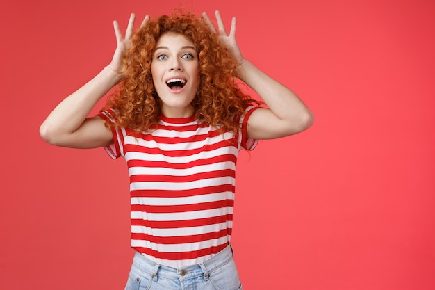 Pod wrażeniem podekscytowany zszokowany młody ładny rudowłosy kędzierzawy imbir dziewczyna reaguje zdumiony zaskoczony niesamowity prezent nie może uwierzyć własnymi oczami chwycić głowę zachwycony otwartymi ustami zasadzkę na czerwonym tle.