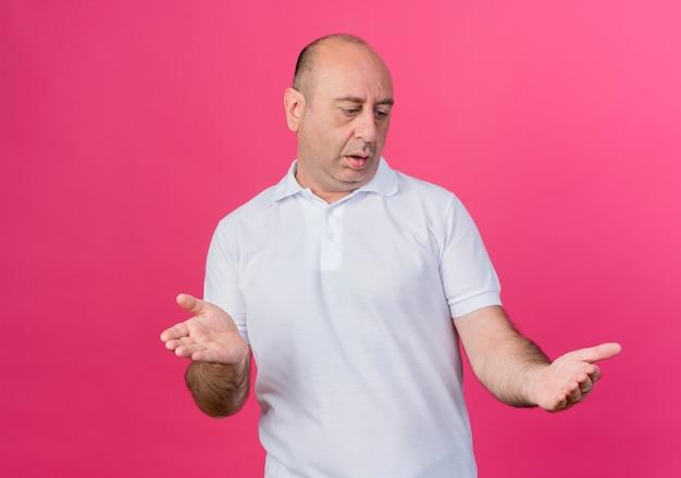 Pod wrażeniem przypadkowy dojrzały biznesmen patrząc na ręce udawać, że trzyma coś na białym tle na różowym tle z miejsca na kopię